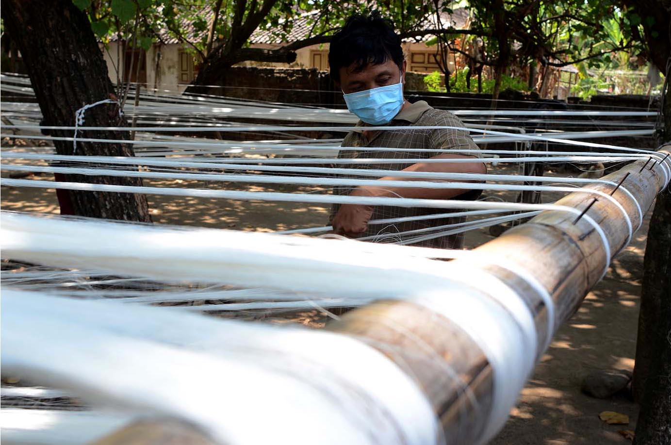 A worker spins threads under a tree. JP/ Magnus Hendratmo
