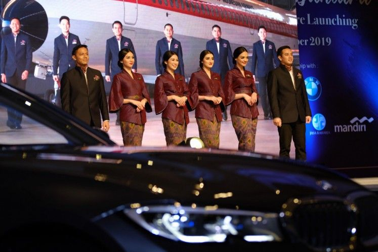 Male and female flight attendants wear new thematic uniforms designed by Didiet Maulana.