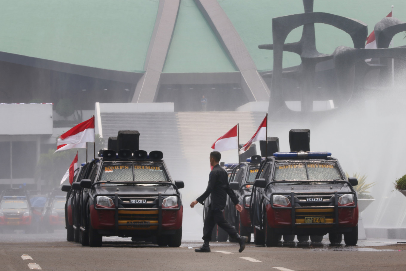 "National Police personnel drive near Senayan Parliament Complex in Jakarta on Thursday. Up to 30,000 Indonesian Military (TNI) and police personnel were deployed to secure the inauguration of President Joko ""Jokowi"" Widodo and Vice President Ma'ruf Amin on Sunday. JP/Dhoni Setiawan"