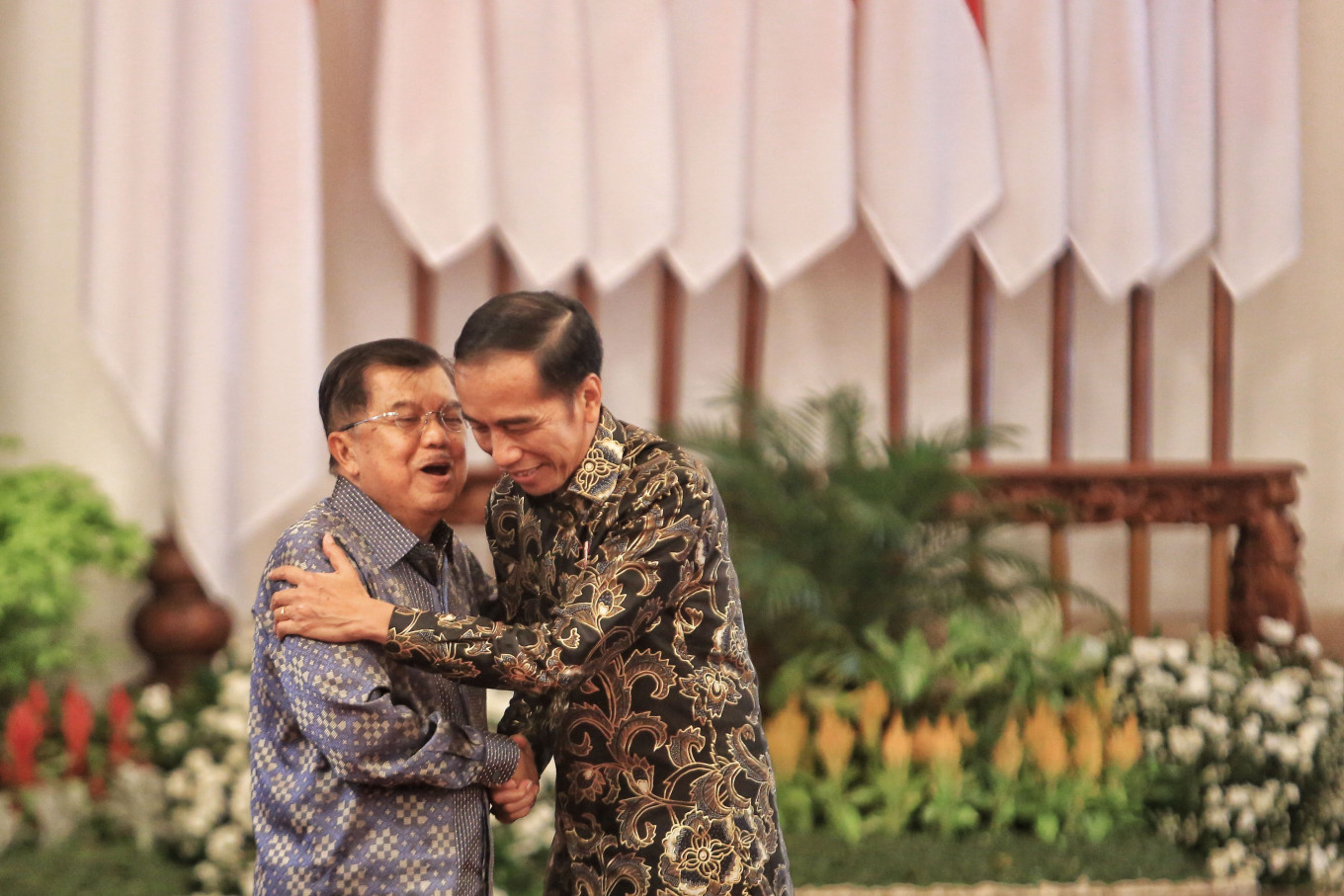 "President Joko ""Jokowi"" Widodo and then-vice president Jusuf Kalla hug one another after a gathering with Cabinet members at Merdeka Palace in Jakarta on Friday. JP/Seto Wardhana"