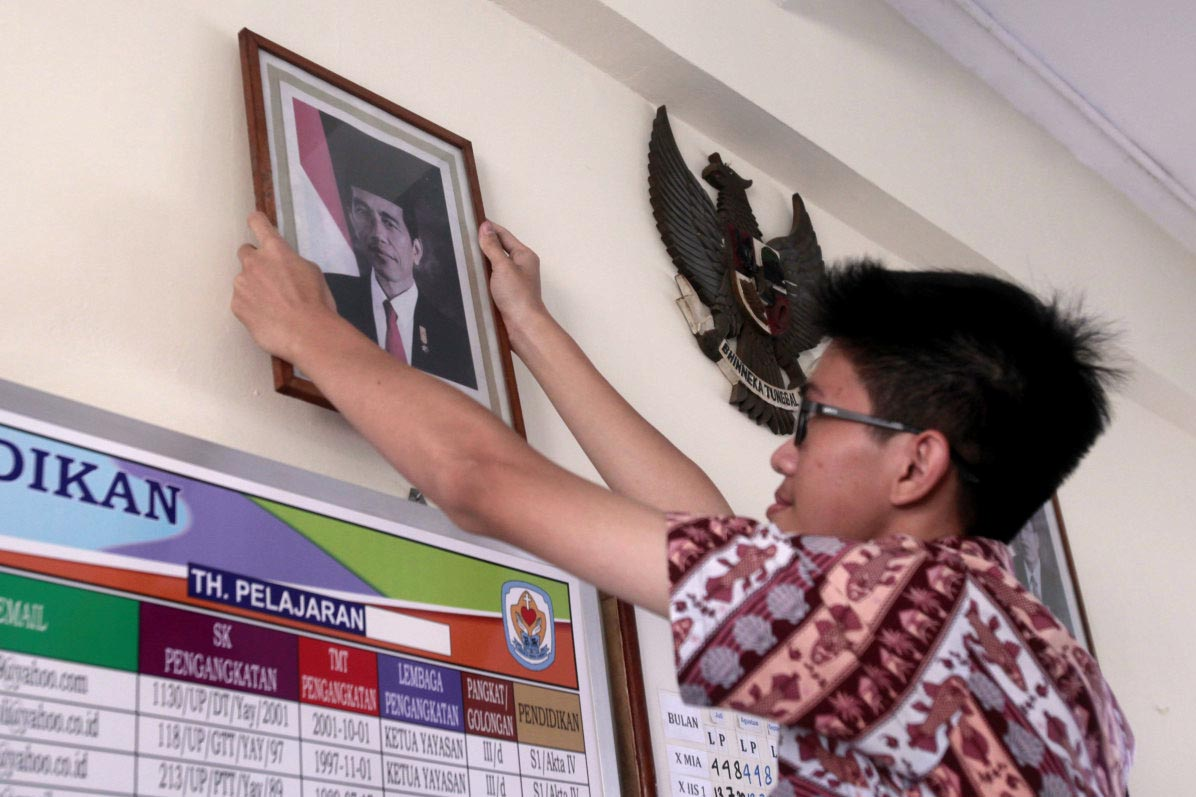 "A student from Tarsisius II high school takes down a picture of President Joko ""Jokowi"" Widodo. The picture will be replaced with new official photos of the President and Vice President Ma'ruf Amin for the 2019-2024 term. JP/Narabeto Korohama"