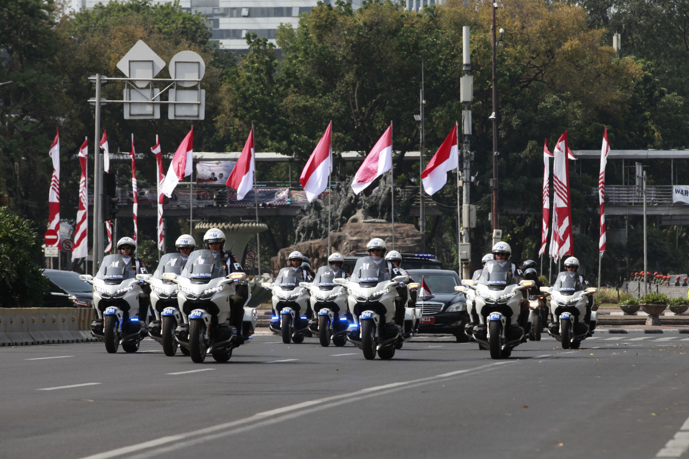 A convoy of vehicles carrying the President passes the front of Bank Indonesia Fountain, Jakarta, on its way to the inauguration ceremony. JP/Narabeto Korohama