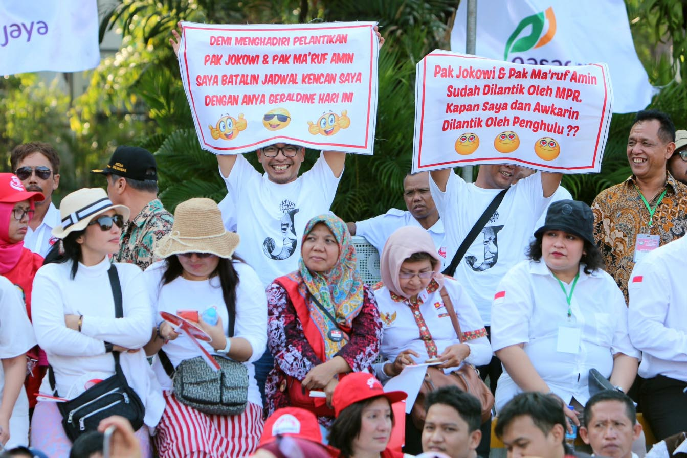 "Supporters of President Joko ""Jokowi"" Widodo and Vice President Ma'ruf Amin gather in front of Merdeka Palace in Central Jakarta on Sunday, Oct. 20. They held up congratulatory messages to express their support for the pair that will lead the country until 2024. JP / Wendra Ajistyatama"