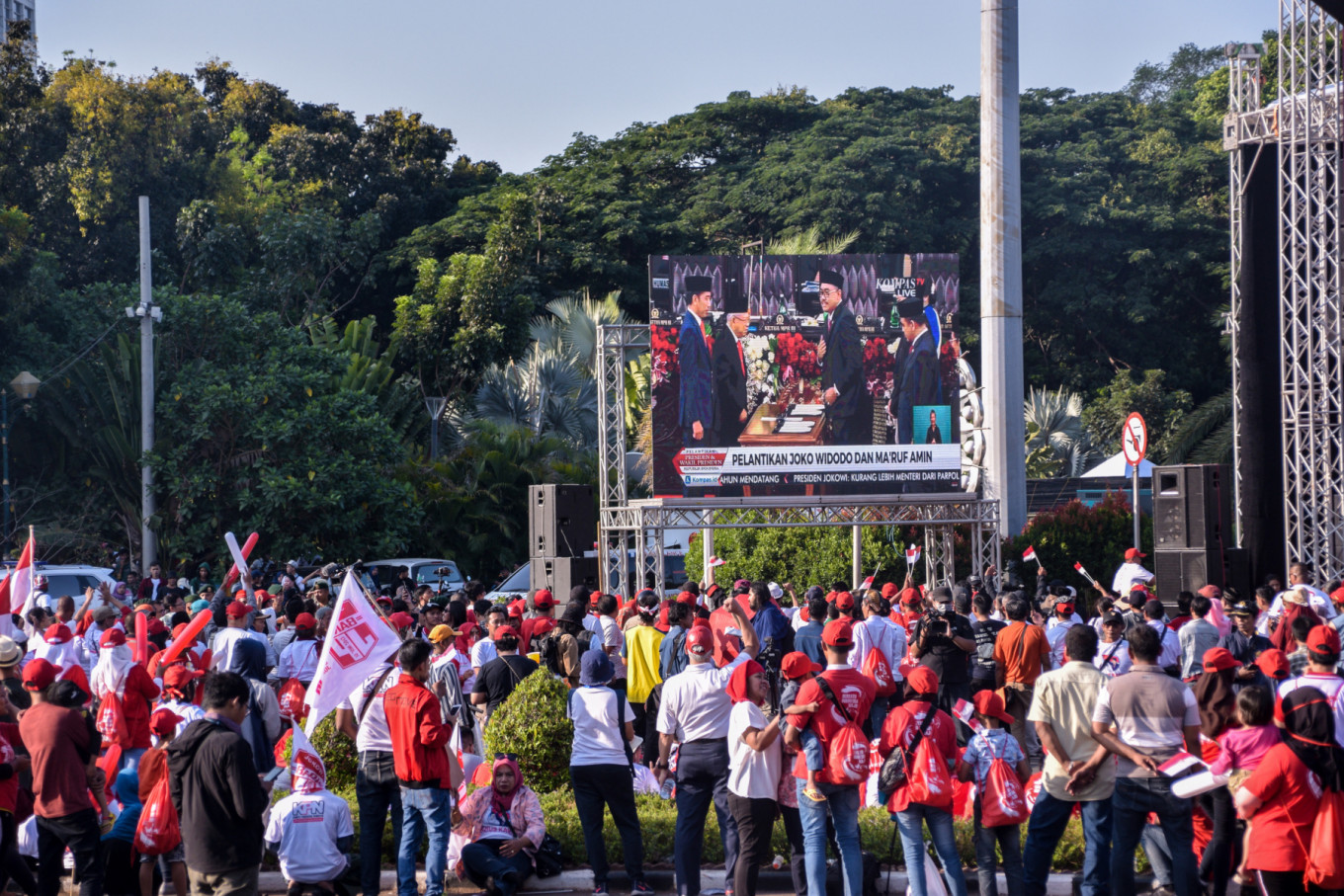 "Supporters of Joko ""Jokowi"" Widodo and Ma'ruf Amin gather to watch the pair be inaugurated as the country's president and vice president on a big screen near the Patung Kuda (Horse Statues) landmark on Jl. Medan Merdeka Barat in Central Jakarta on Sunday, Oct. 20. JP/Anggie Angela"