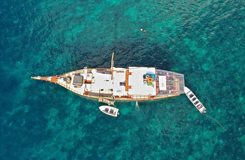 Crystal clear: A bird's-eye view of the Amaya Explorer and a man snorkeling to enjoy the scenery of the reef in Serua Island waters.