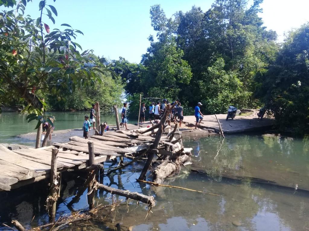 Residents cross a rickety wooden bridge to cross the Wae Musur River in Ranamase district, East Manggarai regency, in East Nusa Tenggara in October.