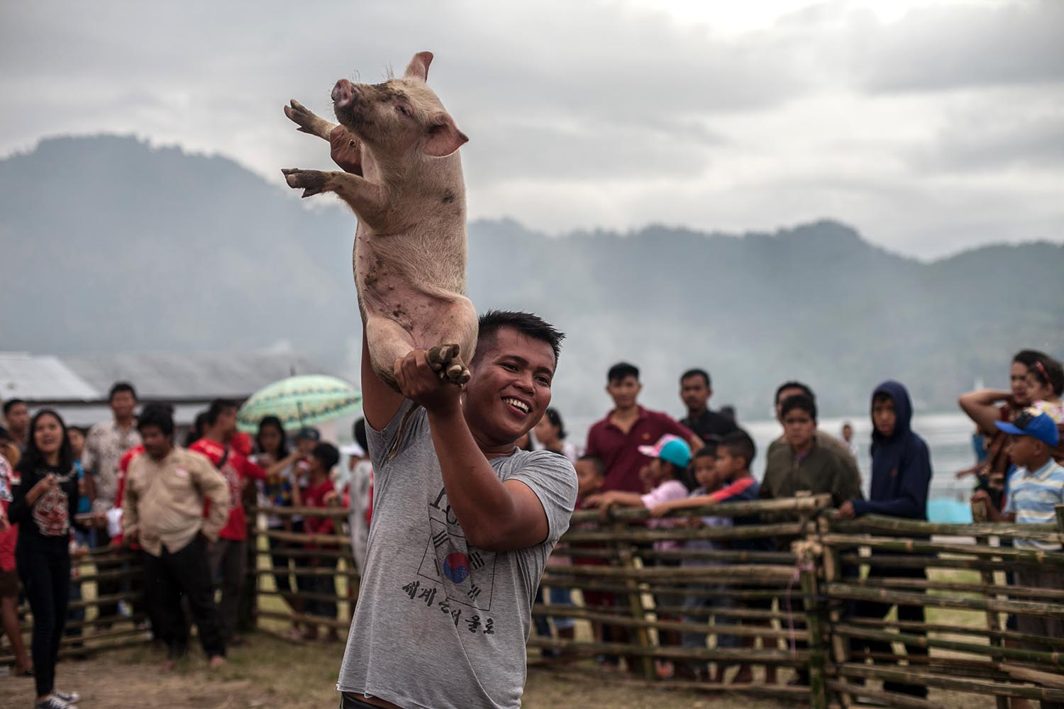 Winner's trophy: Firwan Aritonang is victorious as a pig catcher. JP/Andri Ginting