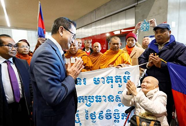 Cambodian opposition figure Sam Rainsy boards plane in Paris