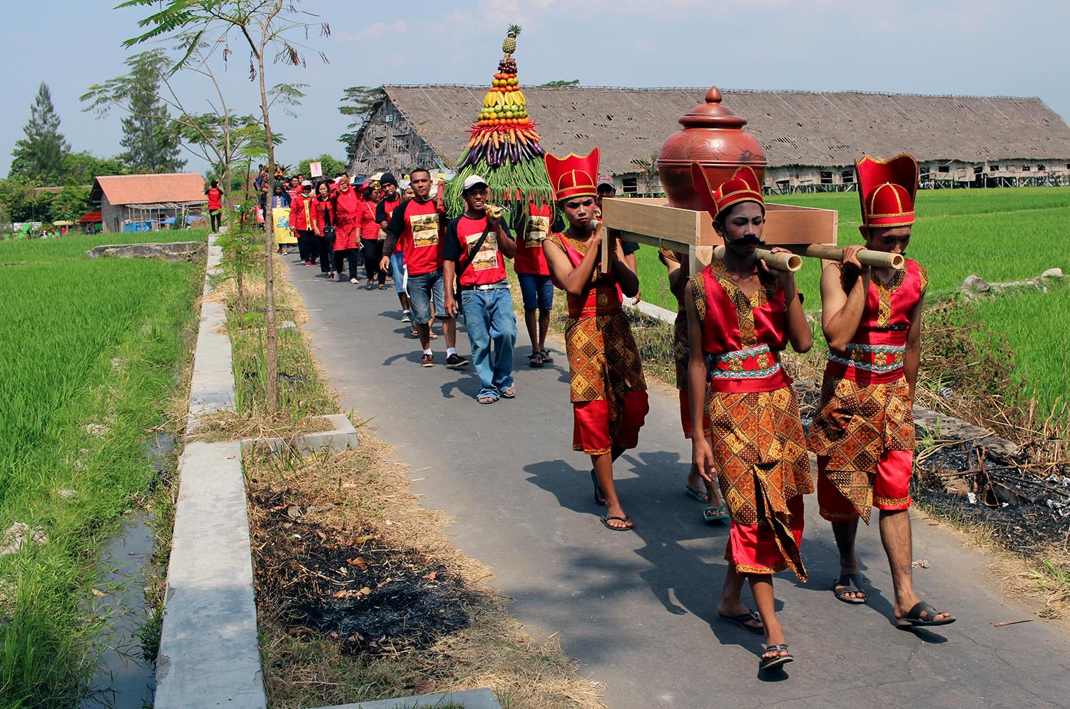 Residents carry clay water jugs, as well as offerings, through paddy fields and Pluneng village. JP/ Magnus Hendratmo