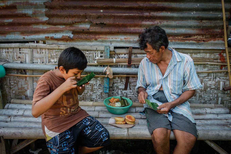 Rizki enjoys traditional snacks with his grandfather, Suyatiman, in the side yard of the house. JP/ Anggertimur Lanang Tinarbuko