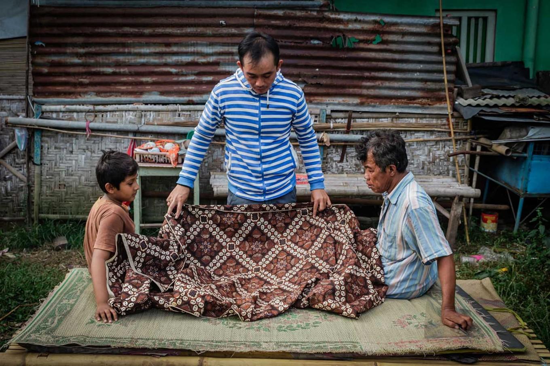 Rizki, Pras and Suyatiman measure jarik cloth. JP/ Anggertimur Lanang Tinarbuko