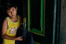 Rizki poses in a Peranakan uniform near the door. JP/ Anggertimur Lanang Tinarbuko