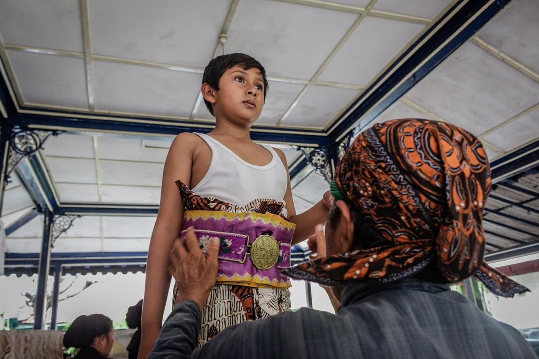 Rizki is assisted by Suyatiman in wearing Javanese traditional attire. The waist strap bears the Praja Cihna (Haba), the official symbol of Kraton Ngayogyakarta Hadiningrat. JP/ Anggertimur Lanang Tinarbuko