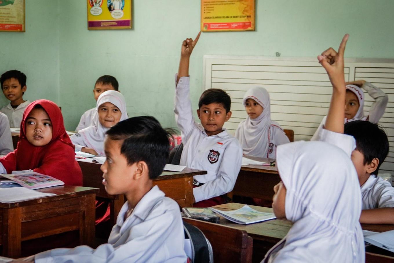 Rizki raises his hand to answer the teacher's question.JP/ Anggertimur Lanang Tinarbuko