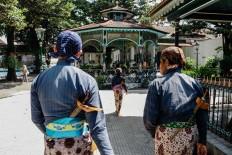 Pras, Rizki and Suyatiman walk to the exit after finishing their duties at the kraton. JP/ Anggertimur Lanang Tinarbuko