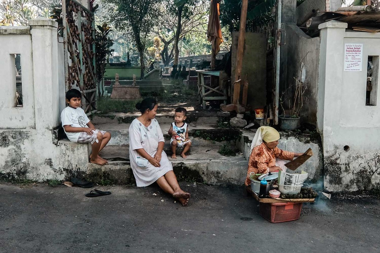 Rizki, his grandmother and brother sit together near a street vendor. JP/ Anggertimur Lanang Tinarbuko