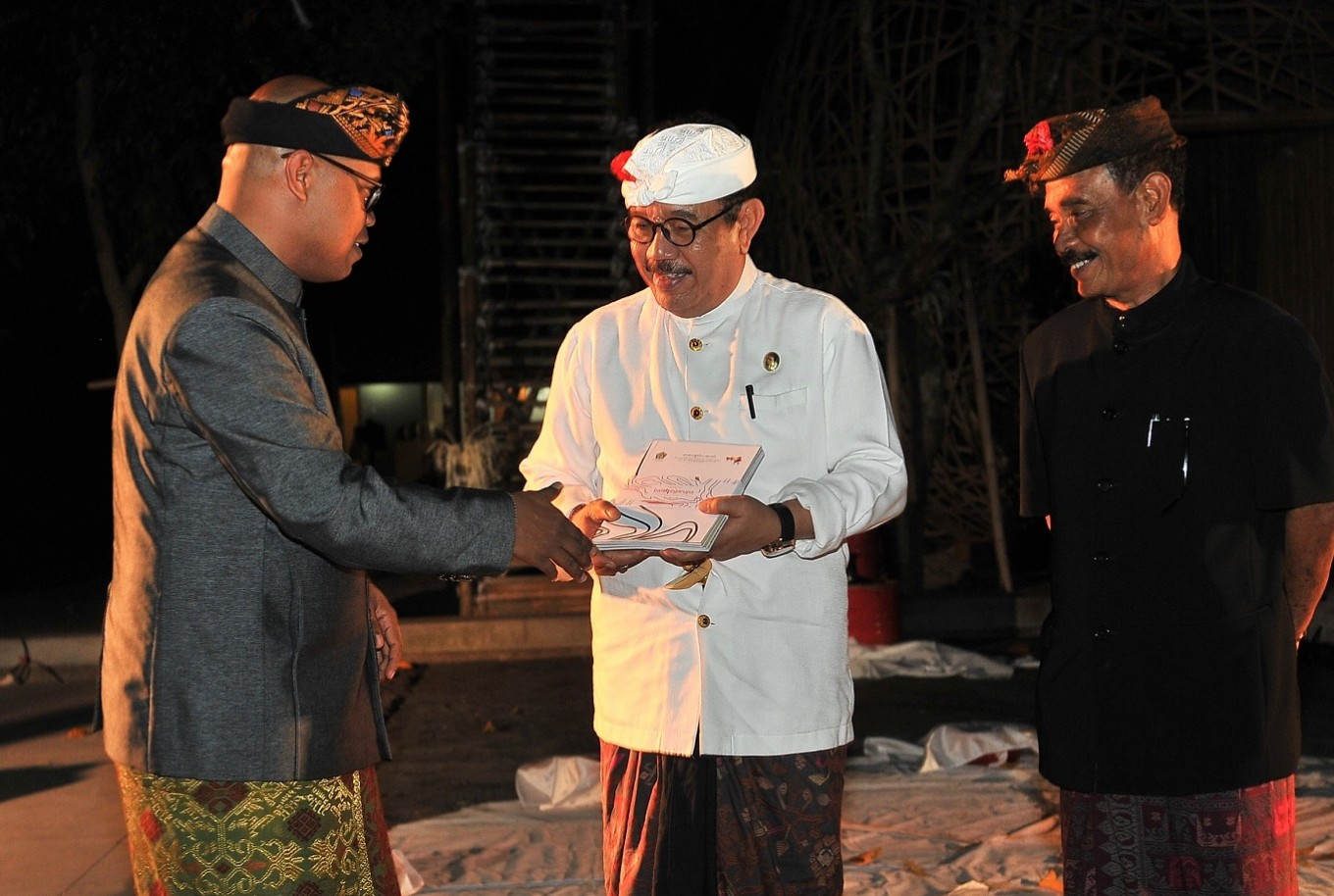 During the opening ceremony of Bali Megarupa on Oct. 10, at ARMA, Dr Wayan Kun Adnyana presents the Bali Megarupa exhibition catalog to Bali Deputy Governor Cokorda Ace as ARMA founder Agung Rai looks on.