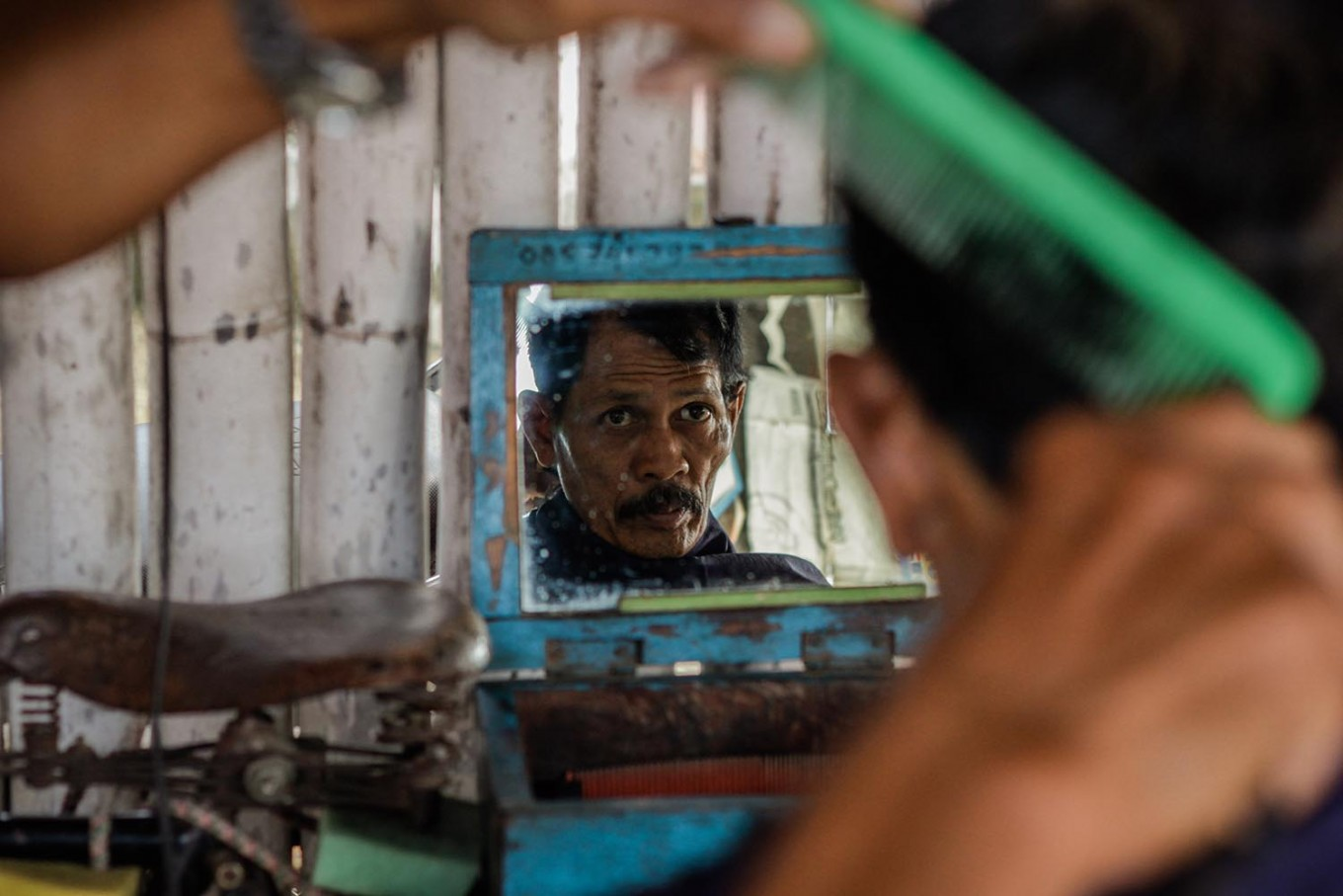 A man observes his haircut from a mirror. JP/Anggertimur Lanang Tinarbuko