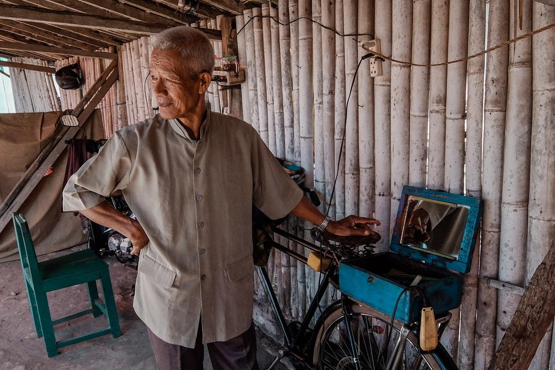 Suhardi waits for customers after preparing his hair-cutting kit at Pasar Turi in Bantul regency, Yogyakarta. JP/Anggertimur Lanang Tinarbuko