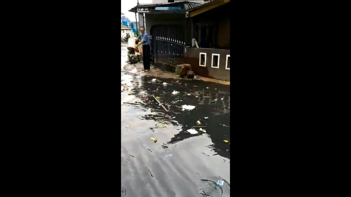 Video: Bandung road becomes river of trash. Man throws more in.