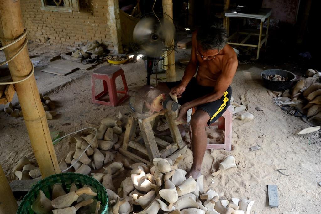 A craftsman at Jambu Kulon village is smoothing a bamboo surface when making 'kentongan' and other bamboo craft works.