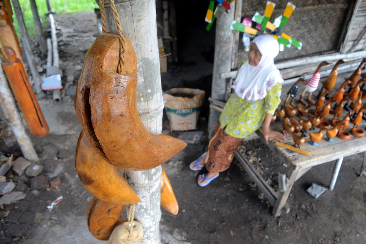 Sri Wito sells 'kentongan' and other bamboo works crafted by her child at a humble kiosk in the outskirts of Jambu Kulon village.