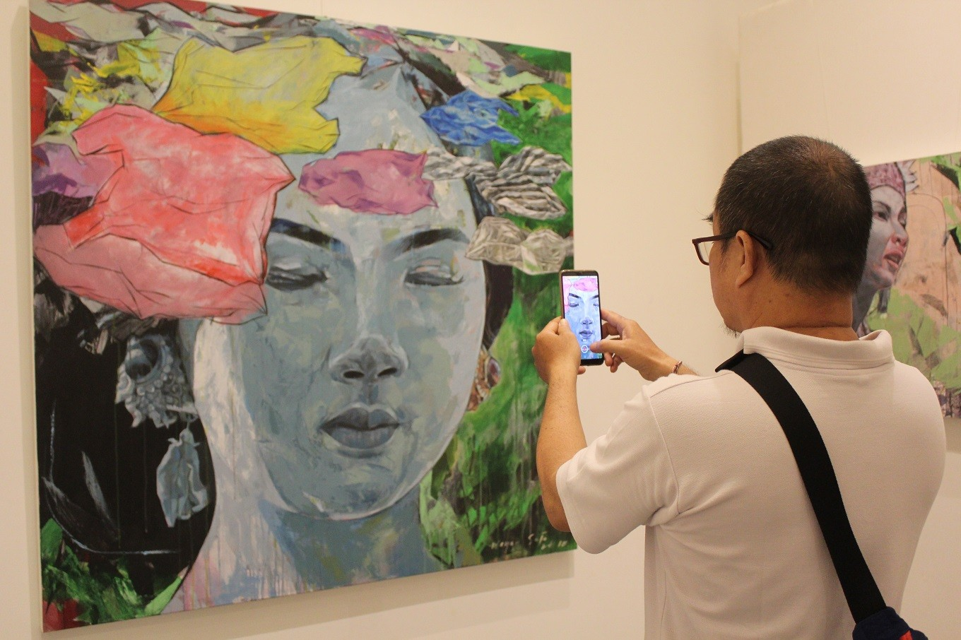 A visitor with a smartphone engages with works by Wayan Suja.