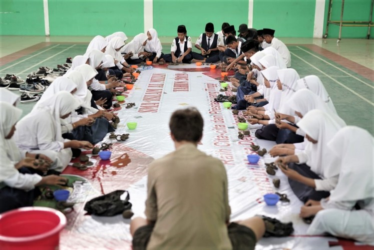 Collaboration: Danish artist Emil Krog Rasmussen and students work on 'Connecting Clay', a public sculpture made of interconnected clay chains, at Al-Mizan Islamic Boarding School in Jatiwangi, West Java.