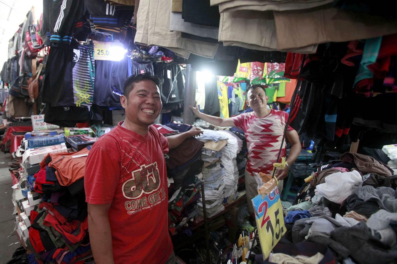 Hustling: Two vendors pose in front of their kiosks at Poncol Market, Central Jakarta. JP/Narabeto Korohama