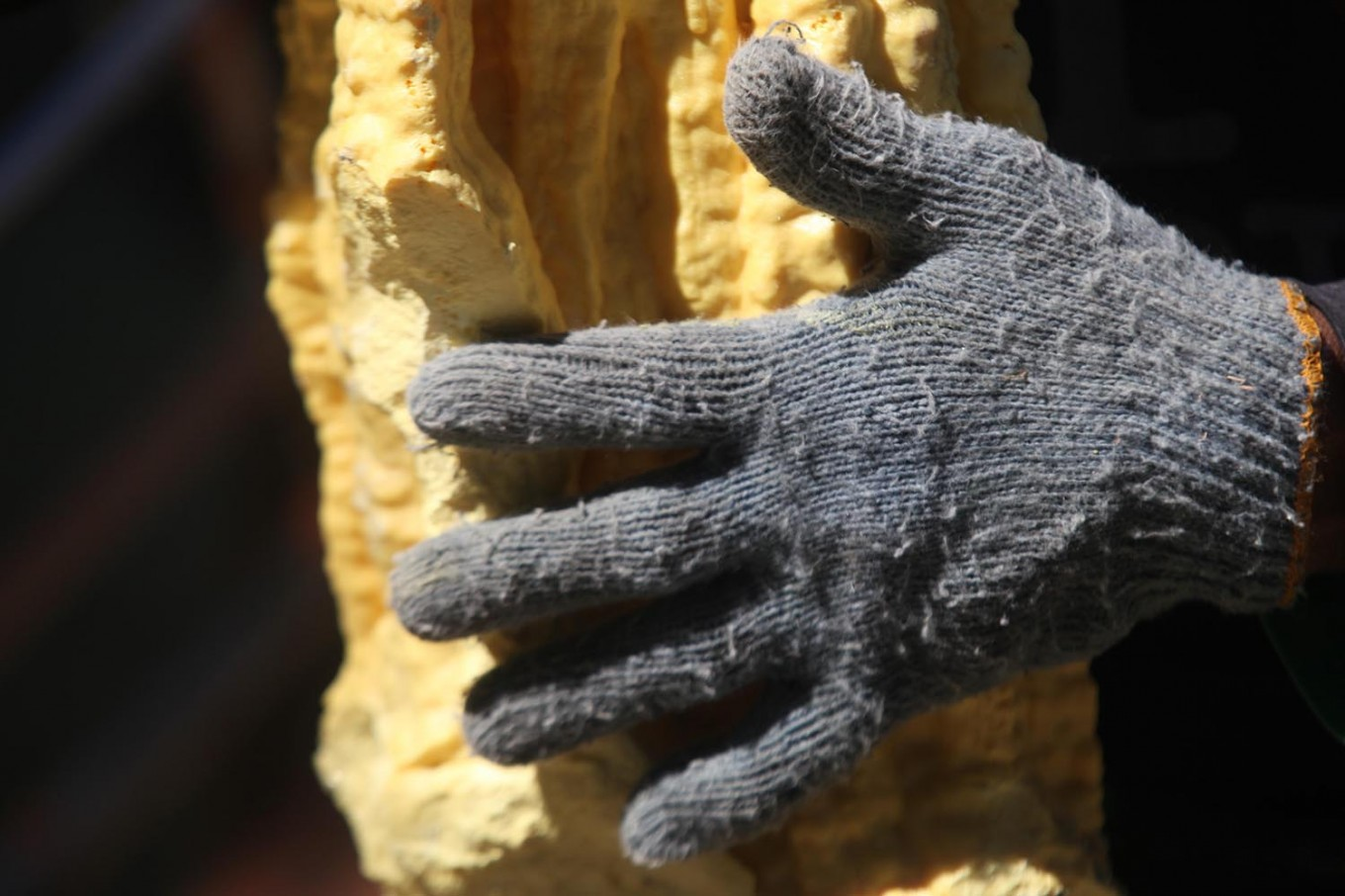 A close-up of a sulfur chunk and a miner's glove. JP/Boy T Harjanto