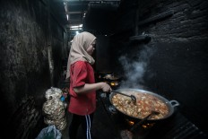 A restaurant staff member cooks food to be served at a Minang-style restaurant in Medan, North Sumatra. JP/Andri Ginting