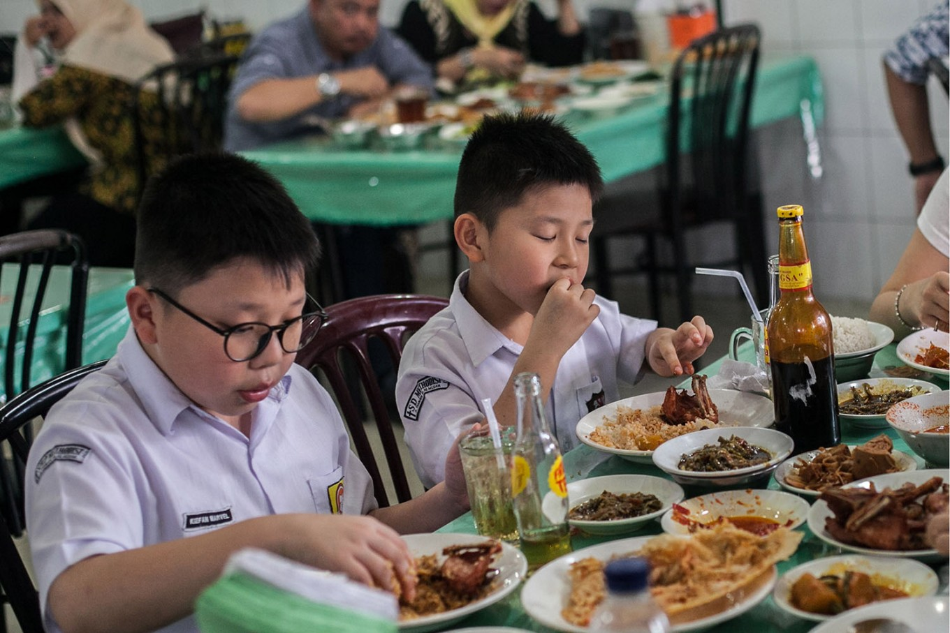 Two children in school uniform enjoy food at a Padang restaurant in Medan, North Sumatra. JP/Andri Ginting