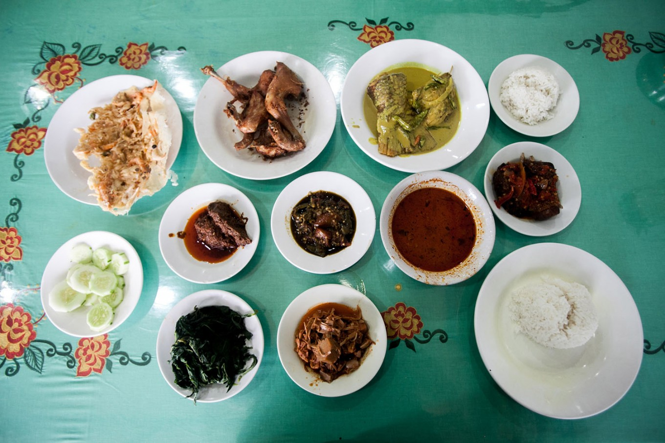 Nasi Padang is spread out on the dining table, comprising steamed rice, beef, chicken and fish dishes, as well as sambal and vegetables. JP/Andri Ginting