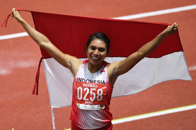 Indonesian track and field star maria Natalia Londa spreads the Red-and-White flag after winning the gold medal in women's long jump during the 30th Southeast Asian (SEA) Games at New Clark Athletics Stadium in the Philippines on Dec. 8, 2019.