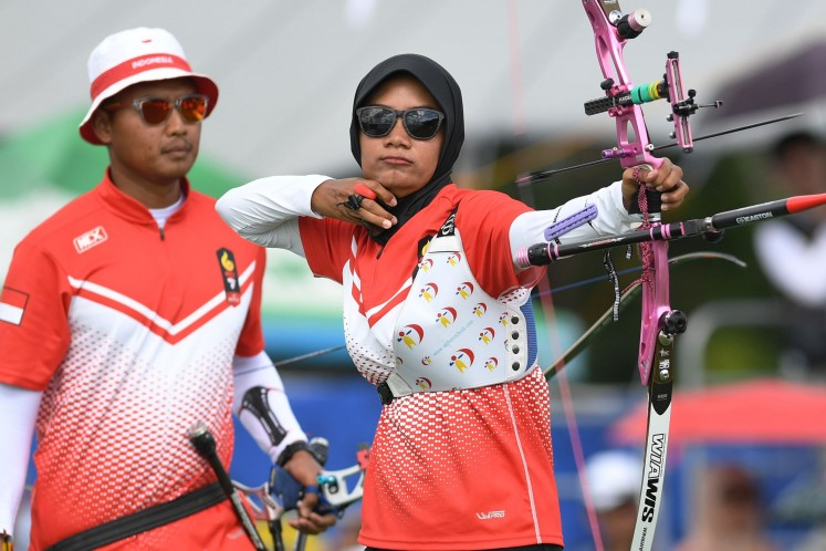 Indonesian archer Choirunisa Diananda (right) releases an arrow as her teammate Riau Ega Agatha Salsabila (left) looks on, during the mixed team recurve final on Dec. 8, 2019 at the 30th SEA Games in Pampanga, the Philippines. The Indonesian pair won silver after losing to Vietnam's Loc Thi dao and Nguyen Hoang Phi Vu.