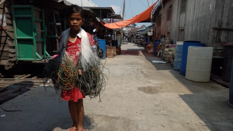 A girl carries fishing nets through the village. Most of the residents work as fishermen.