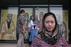 Converse with God: A woman poses in front of the Janasuci Petrus & Paulus Church in Tangerang  as others enter.  JP/ Taufan Wijaya