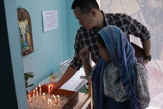 Illuminate the world: Orthodox Church members light candles at the Janasuci Petrus & Paulus Church in Tangerang. JP/ Taufan Wijaya