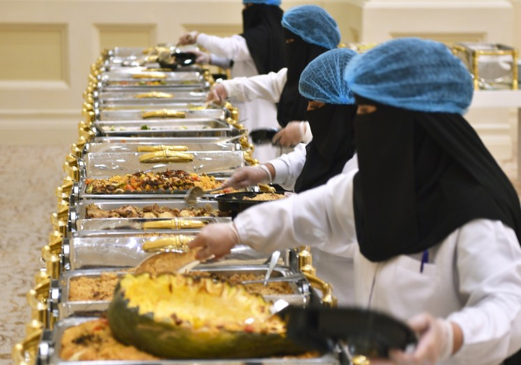 Saudi volunteers, with the Saudi Food Bank or Etaam, pack leftovers into boxes after a wedding in Riyadh on July 3, 2019.