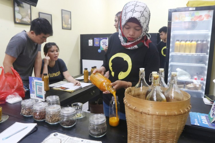 An employee of Jamu Mbak Suni in the BSD Modern Market in South Tangerang, Banten is pouring jamu for young customers on Tuesday.