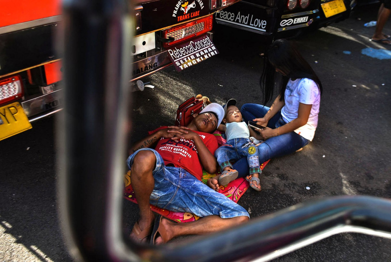 Quick nap: A driver and his family rest up under a truck at the 