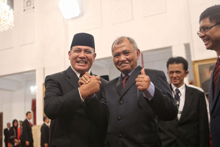 Taking the reins: Corruption Eradication Commission (KPK) chairman Comr. Gen. Firli Bahuri (left) and Agus Rahardjo, head of the antigraft body for the 2015-2019 period, smile as they shake hands after the inauguration of the new KPK leadership and supervisory council members at the State Palace in Jakarta on Dec. 20, 2020.