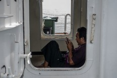 A passenger relaxes on the ferry while using his cell phone. JP/Rosa Panggabean