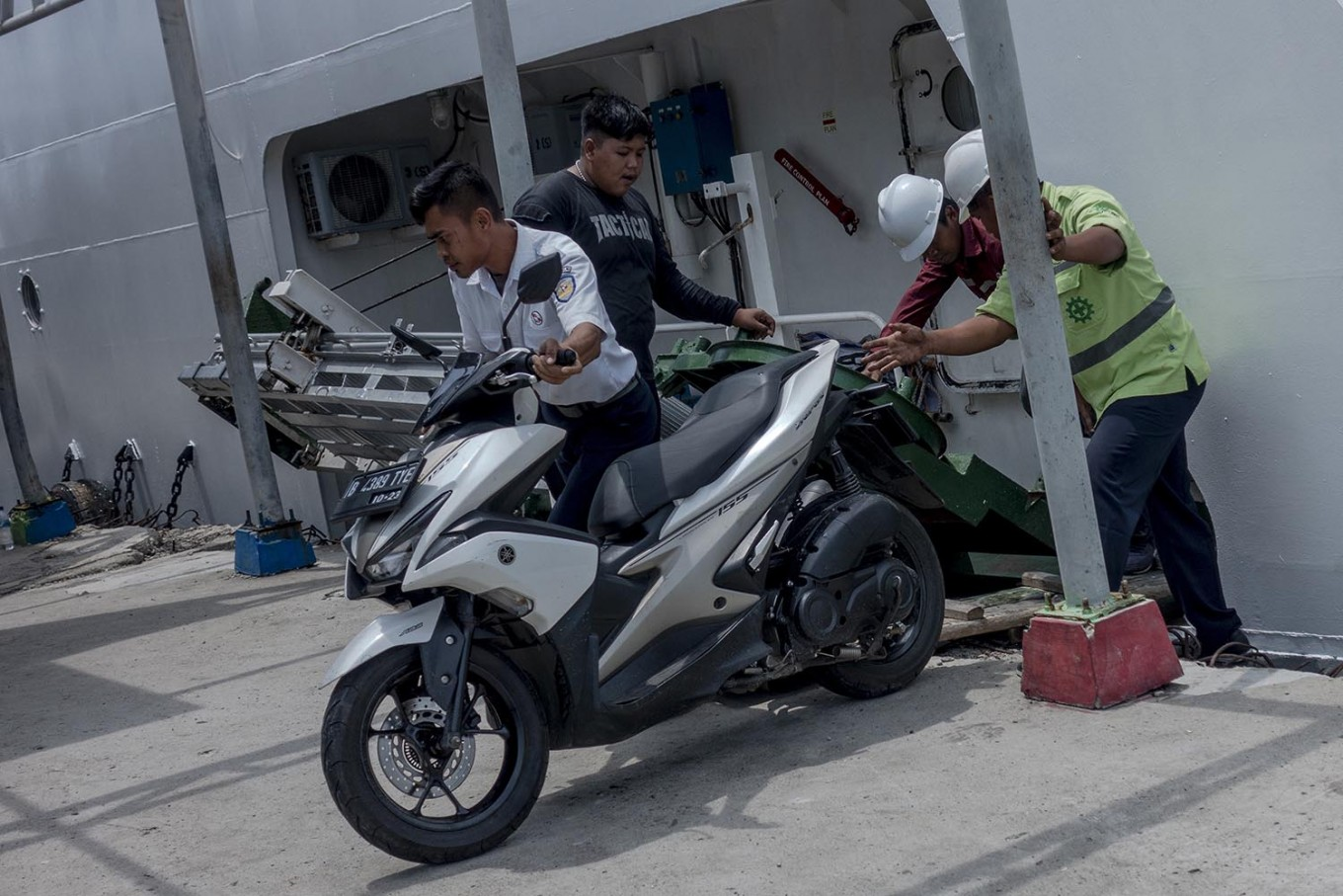 Attendants help unload a motorcycle from the ferry at Pulau Pramuka docks. JP/Rosa Panggabean