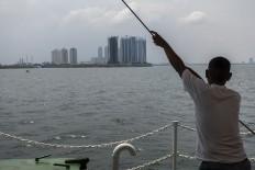 A ferry passenger views Jakarta's skyscrapers. JP/Rosa Panggabean