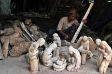 Sriyono carves a bamboo root at his house. The figures will be sent to South Korea.  JP/Magnus Hendratmo