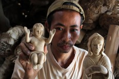 The artist holds figures he created out of bamboo root. JP/Magnus Hendratmo