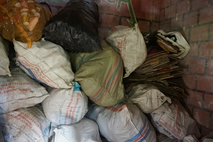 Piles of household waste are gathered at the waste bank. Plastic still dominates the trash dropped off by the locals, although they also gather cardboard boxes and scrap metal.