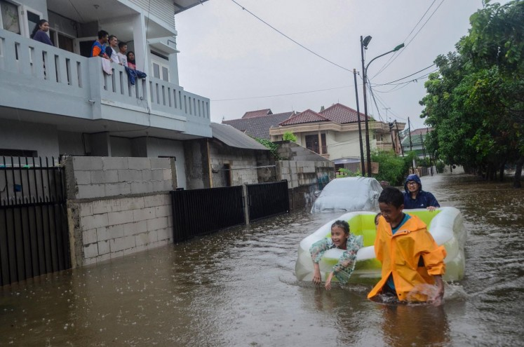 Residents travel using a dinghy on Wednesday morning in a flooded housing area in Duren Sawit, East Jakarta.