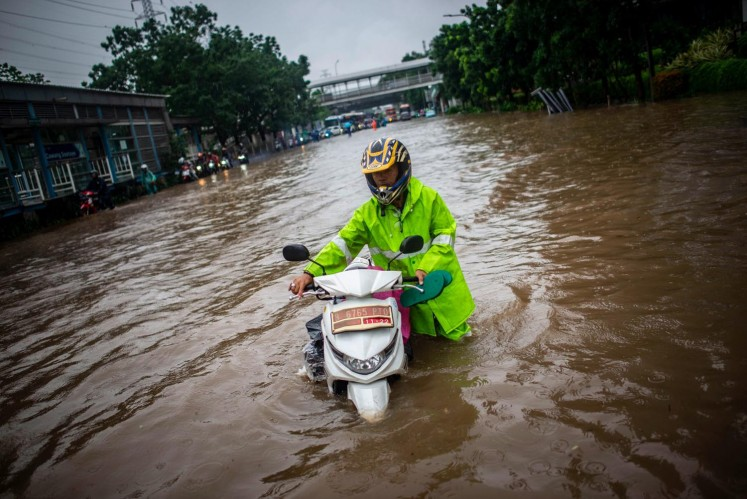 A motorcyclist pushes his vehicle down the middle of a flooded street in East Jakarta on Wednesday.